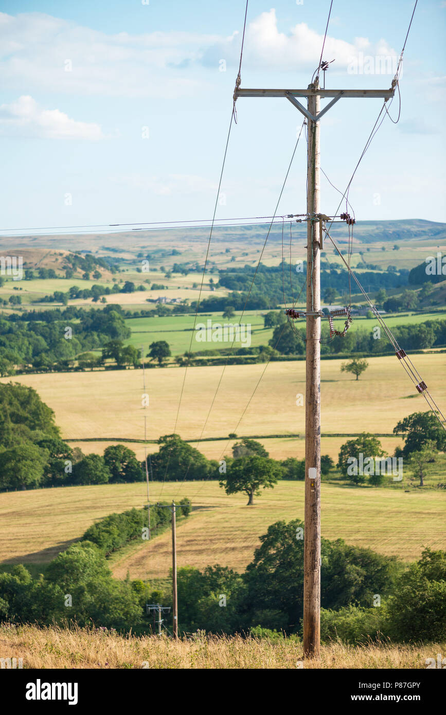 Overhead power cables stretch out across the UK countryside - Stock Image