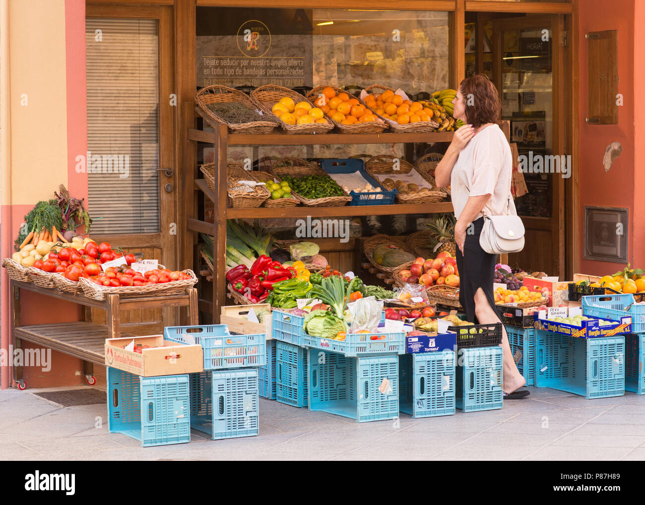 A woman chooses fruit from a display outside a fruit shop - Stock Image