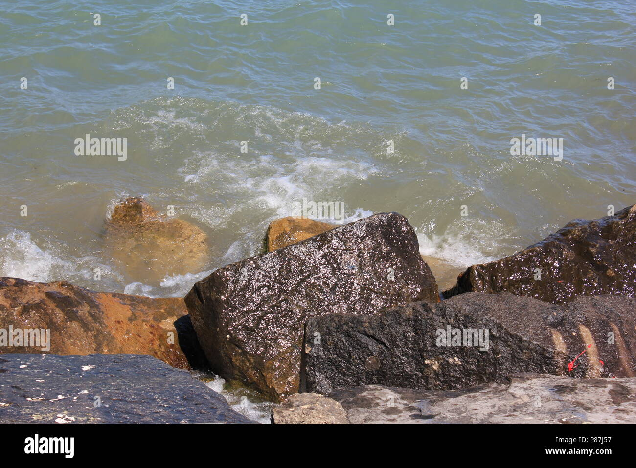 Broken rocks at the lakefront at Northwestern University Park on the Lake in Evanston, Illinois on a beautiful sunny summer day. - Stock Image