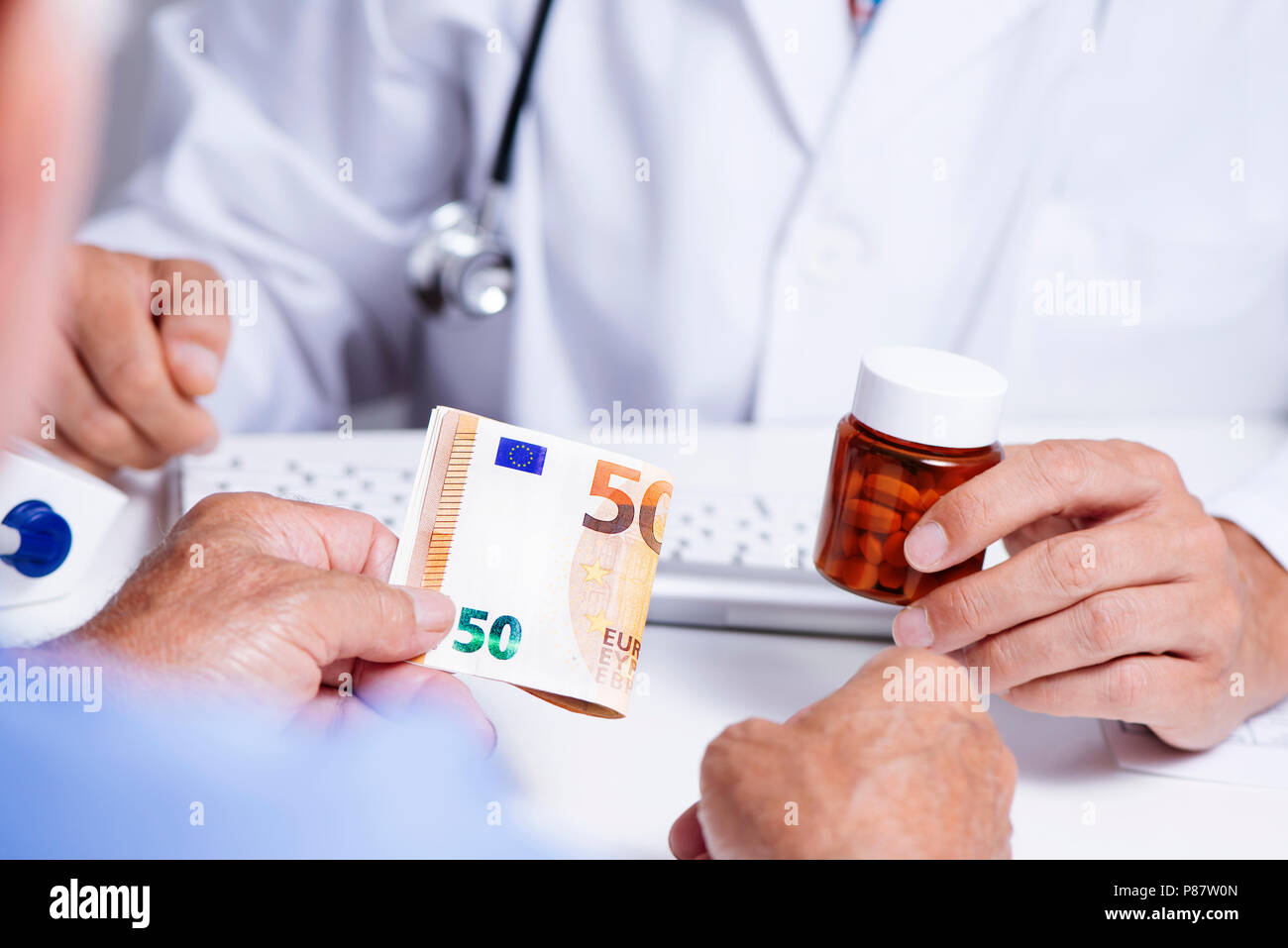 closeup of a caucasian doctor man, in a white coat, giving a bottle of pills to a senior caucasian patient man, who is giving to the doctor a 50 euro  - Stock Image