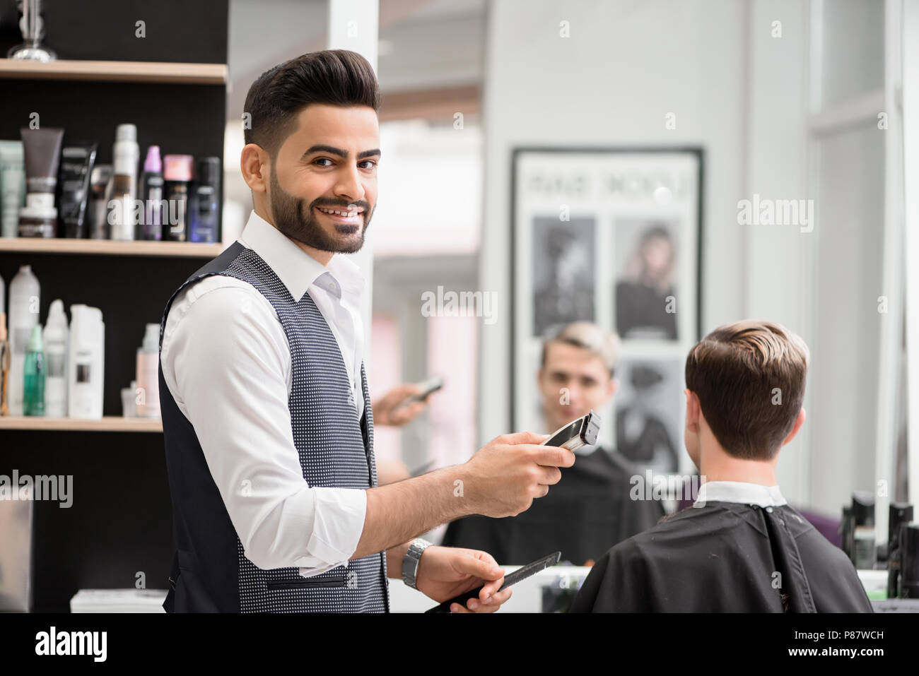 Smiling barber making hairdress for young client in barbershop. Hairdresser holding sharp scissors and plastic comb, wearing white shirt, grey waistco - Stock Image