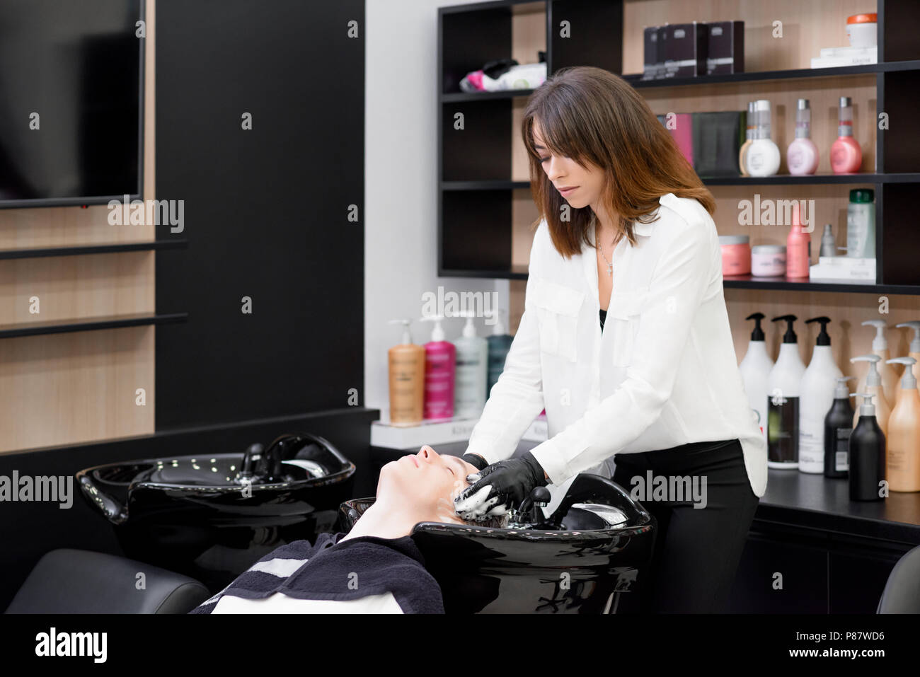 Female hairdresser washes client's head in beatysalon. Young boy's head lying in black washstand. Hairstyler using professional shampoes and balms for - Stock Image