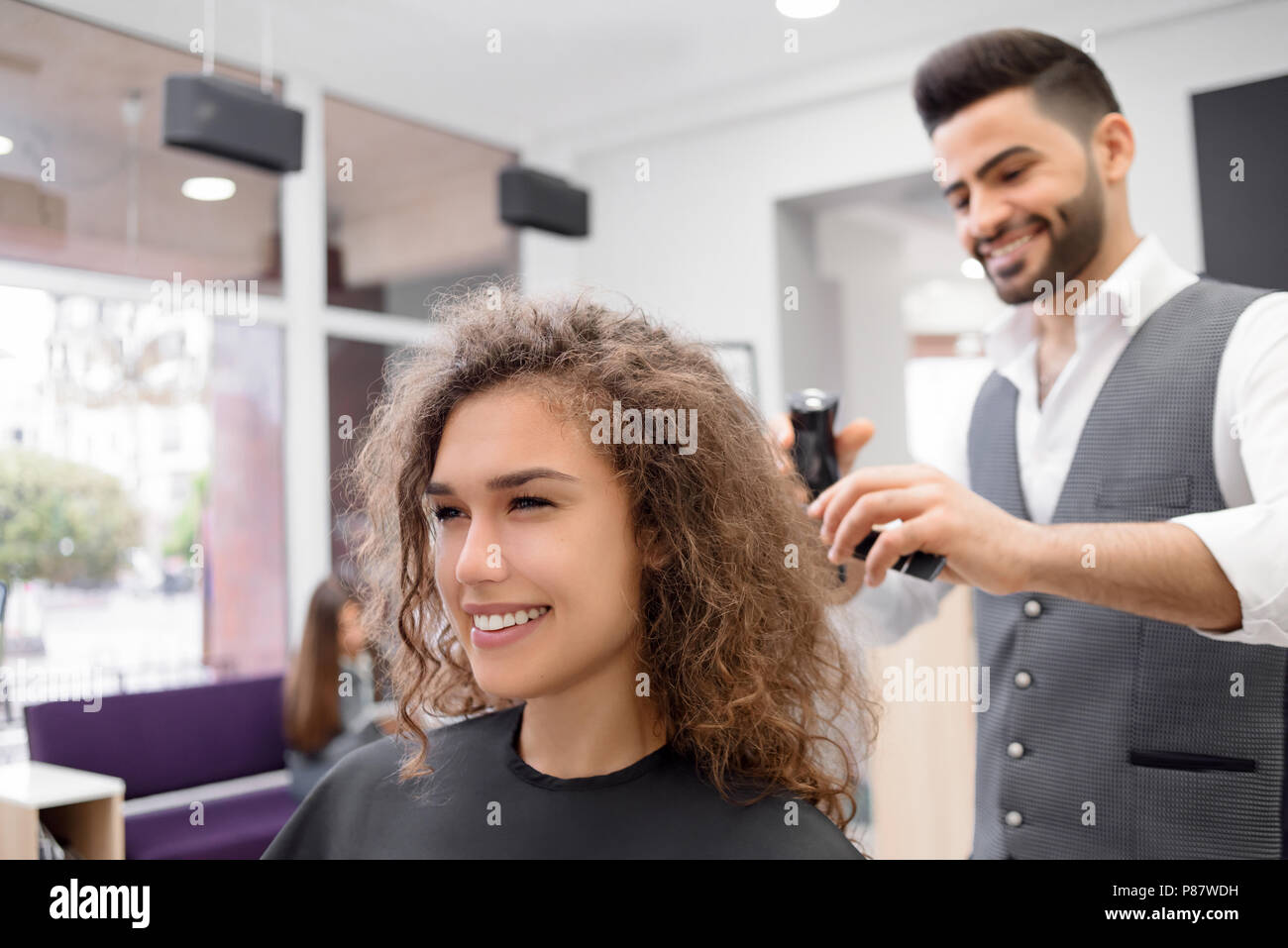 Young haircutter doing hairdress for smiling curly female client. Using plastic comb and barber machine. Wearing white shirt, grey waistcoat. Working  - Stock Image