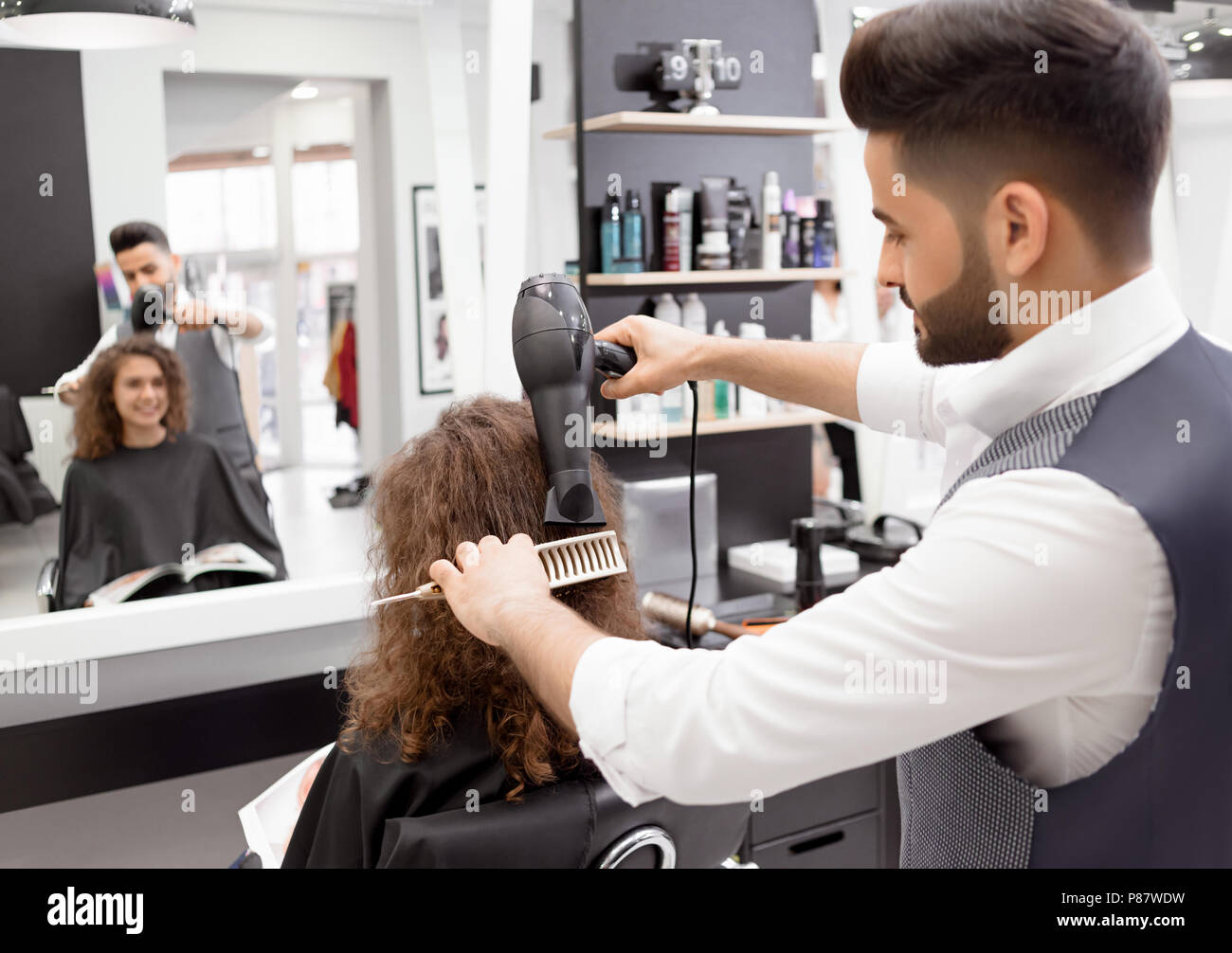 Backview of hairstyler doing hairdress for smiling curly female client. Blurred reflection in big mirror. Using plastic brush and hair dryer. Wearing  - Stock Image