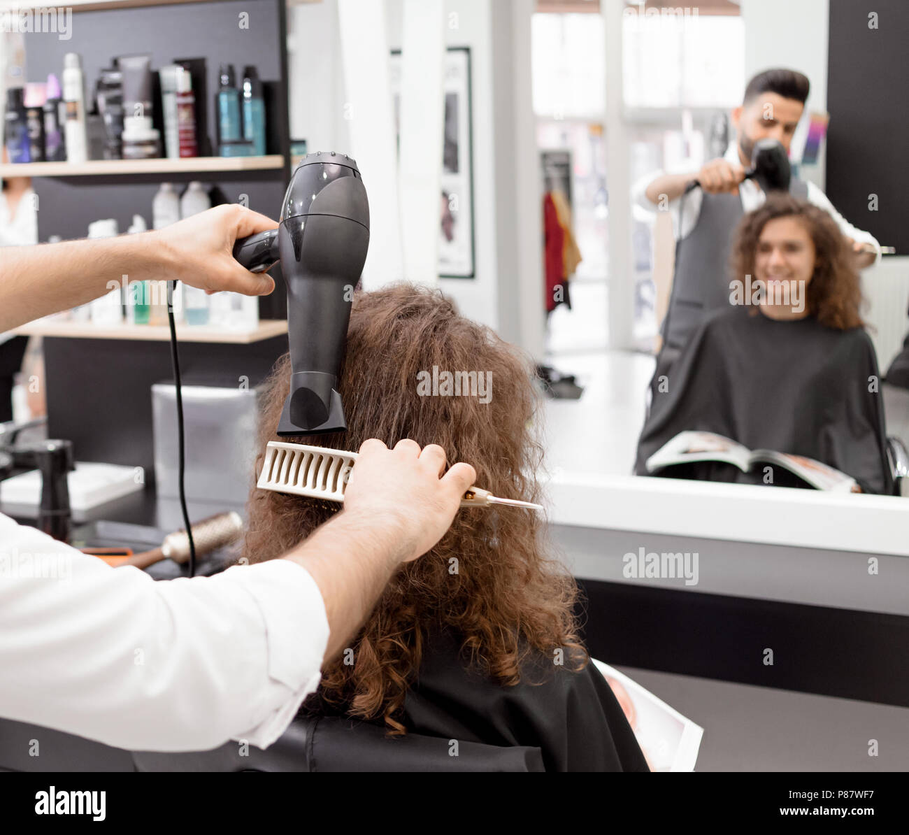Backview Of Hairstyler Drying Female Clients Curly Hair Blurred