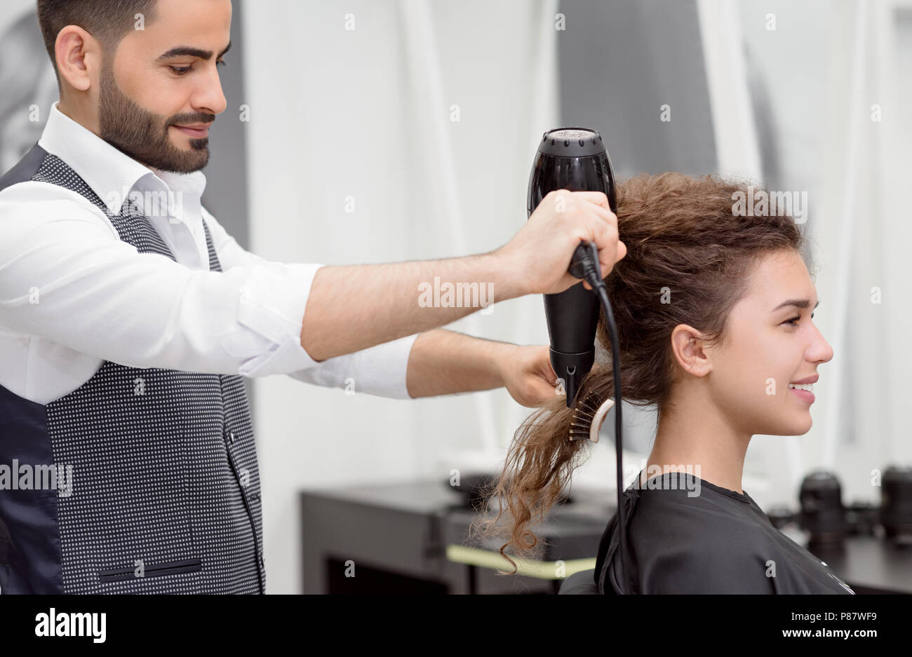 Sideview of Arabian hairstyler drying smiling female client's curly hair. Blurred reflection in big mirror. Using plastic brush and hair dryer. Wearin - Stock Image