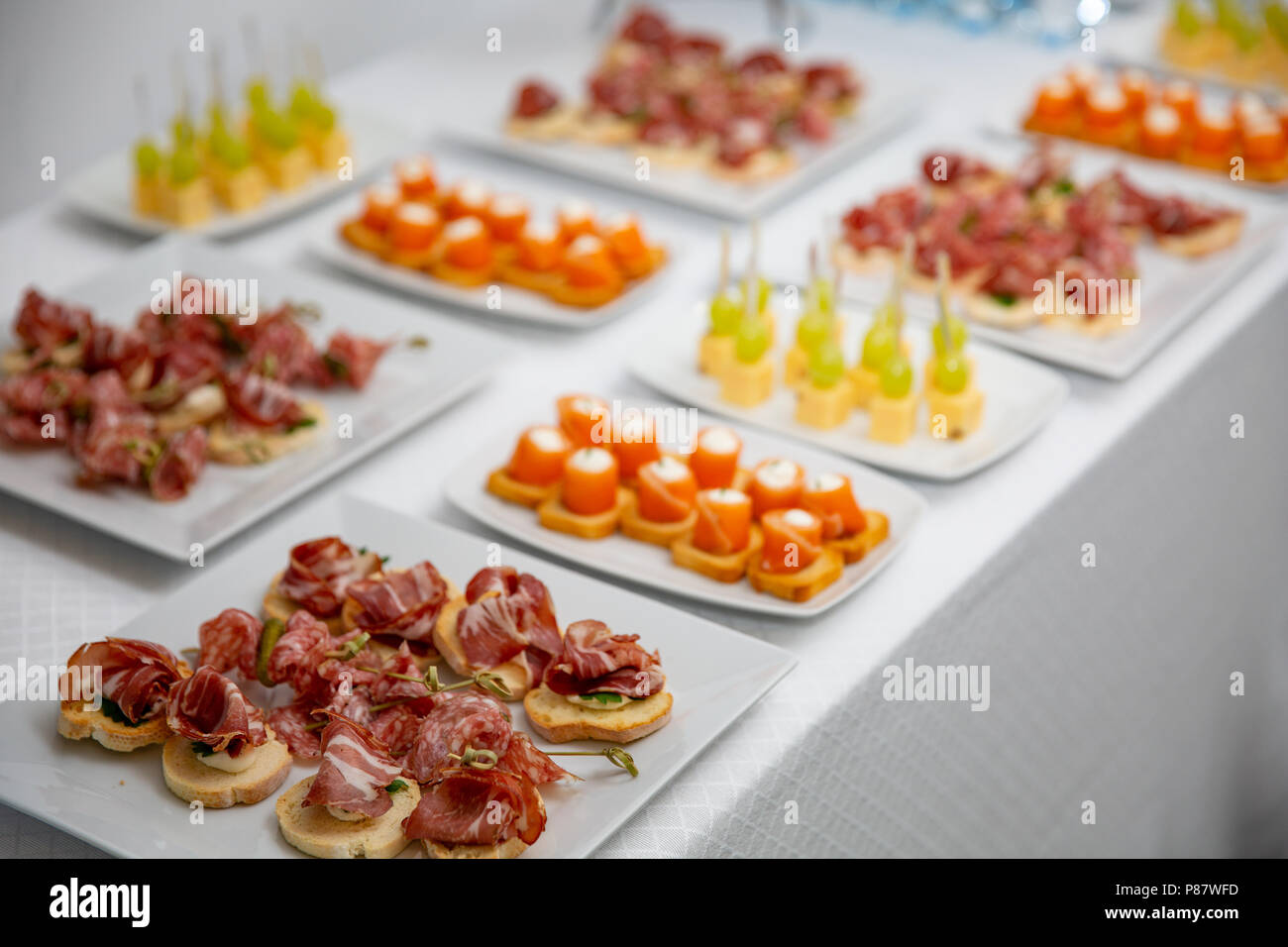 Set a variety of canapes and snacks on a table at the restaurant to celebrate the wedding or other solemn event. - Stock Image