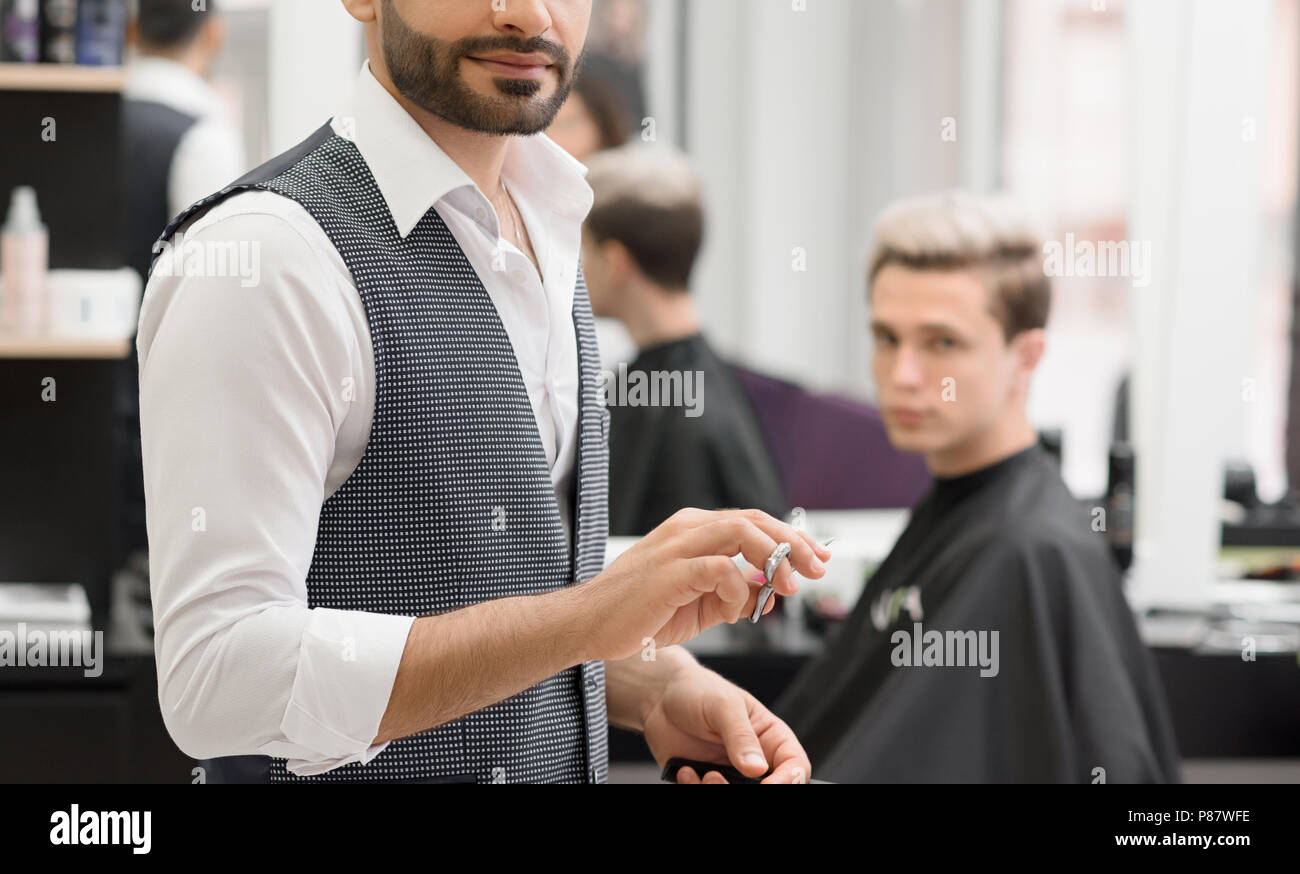 Cropped photo of hairdresser working in barbershop using scissors. Wearing white classic shirt, grey waistcoat. Making fashionable, stylish haircut fo - Stock Image