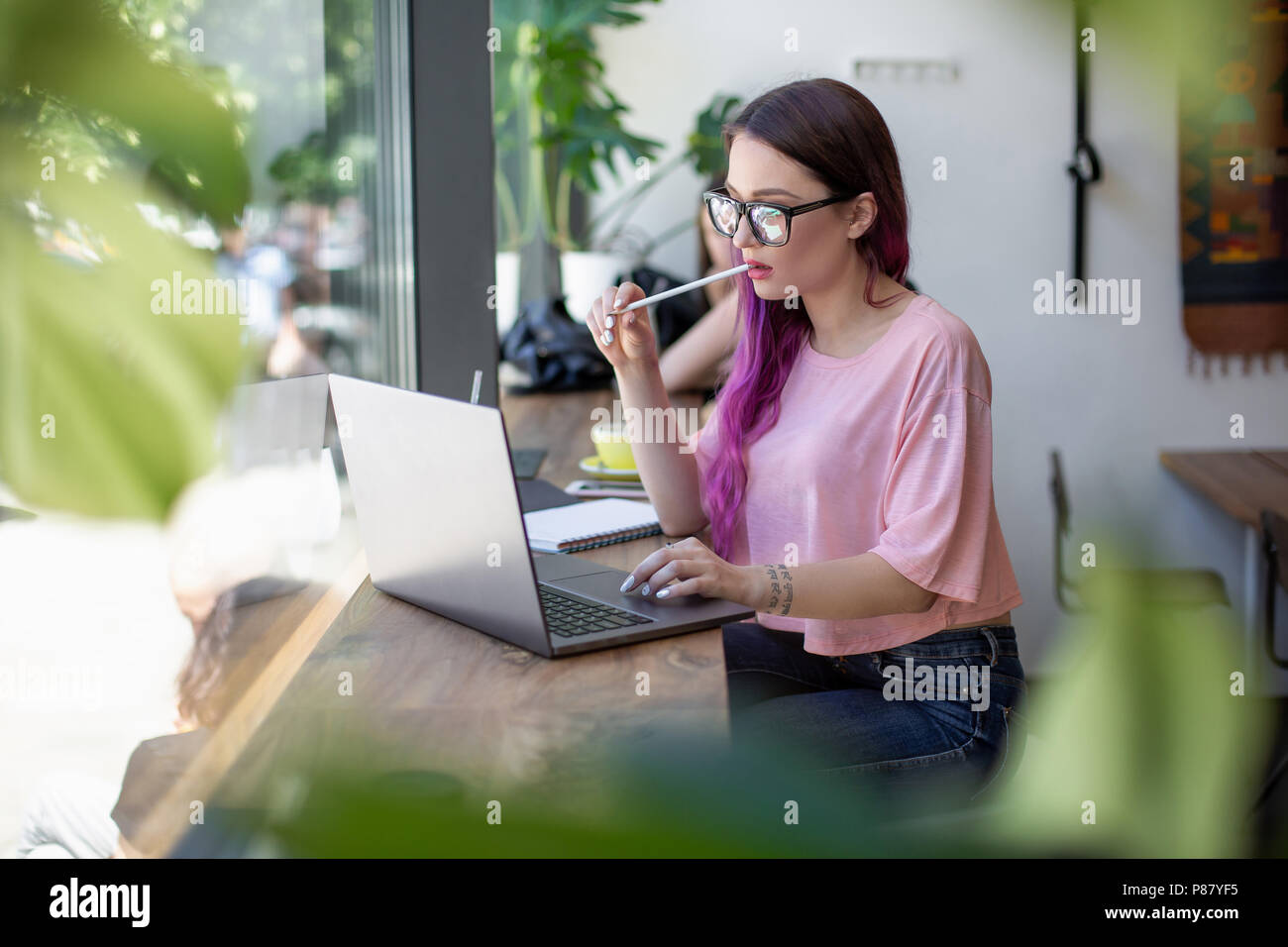 Side view of young businesswoman sitting at table in coffee shop. On table cup of coffee and laptop. In background white wall and window. - Stock Image