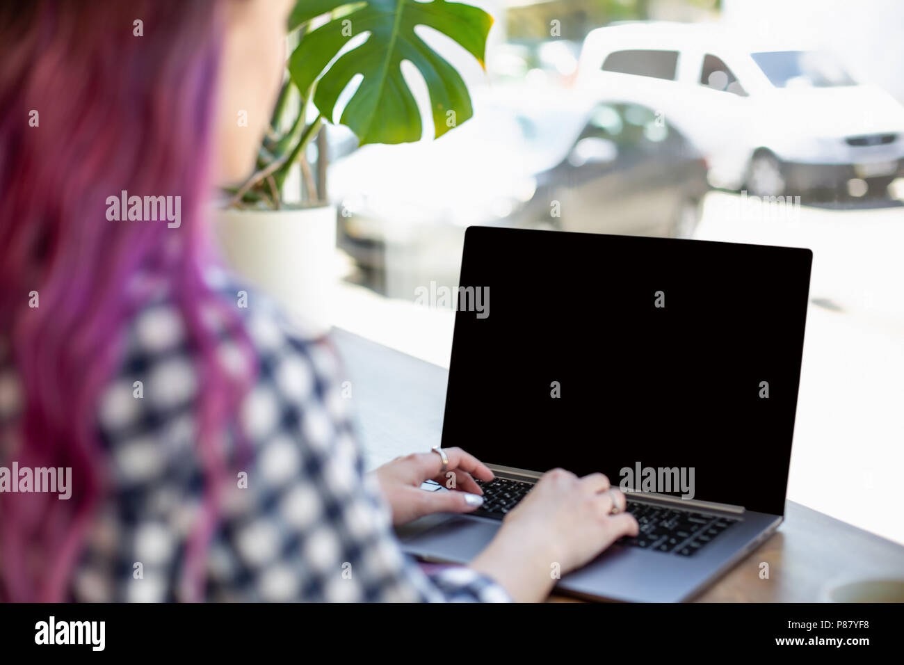 Back view of a young pink hair woman keyboarding on laptop computer with blank copy space screen while sitting in cafe. - Stock Image