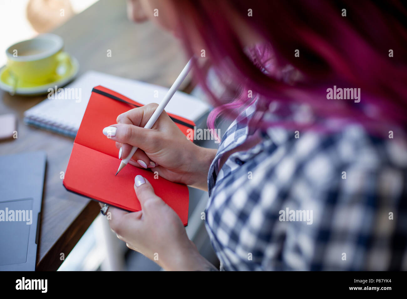 Positive female student with pink hair writing down funny story in notebook sitting in coffee shop with cup of cappuccino and laptop. - Stock Image