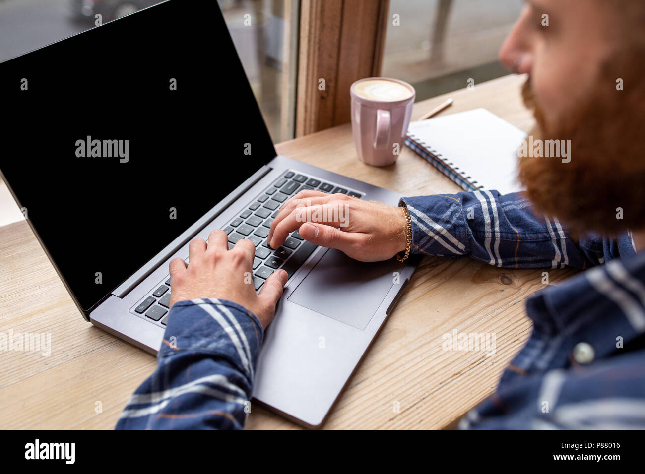 Cropped image of young man chatting via net-book during work break in coffee shop, male sitting in front open laptop computer with blank copy space screen. - Stock Image