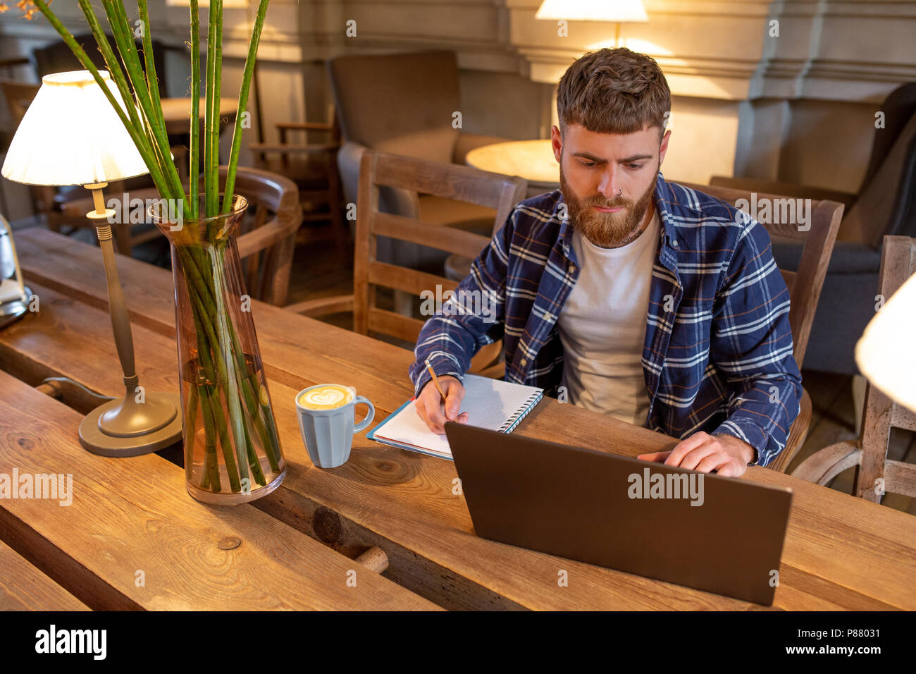 Casual business man or freelancer planning his work on notebook, working on laptop computer with smart phone, cup of coffee on table at coffee shop or home office. - Stock Image
