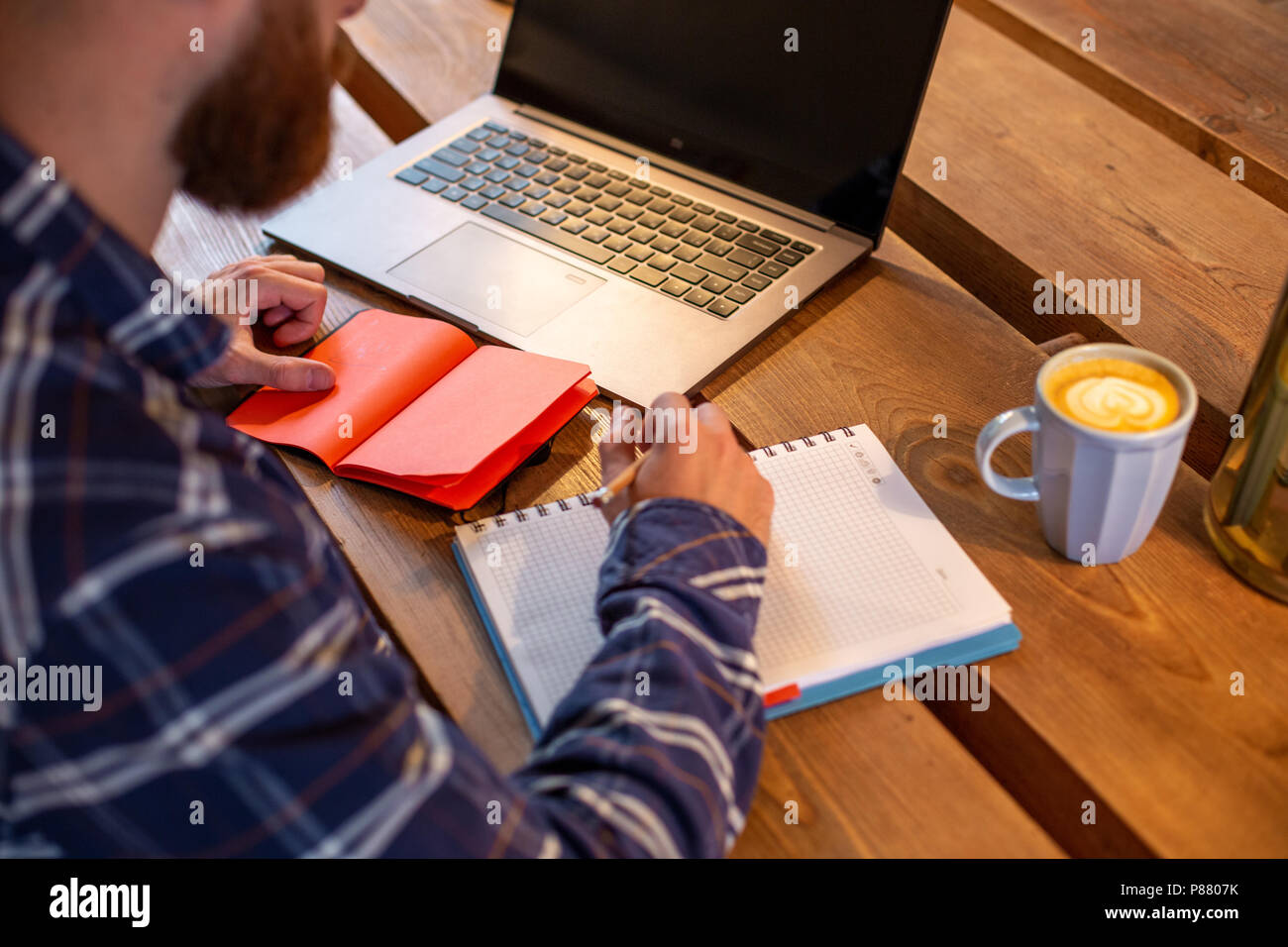 Cropped image of casual business man or freelancer planning his work on notebook, working on laptop computer with smart phone, cup of coffee on table at coffee shop or home office. - Stock Image