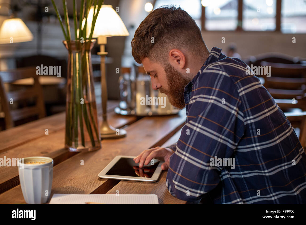 Freelancer dressed in casual outfit focus on reading news and looking on digital tablet while sitting in cozy urban cafe. - Stock Image