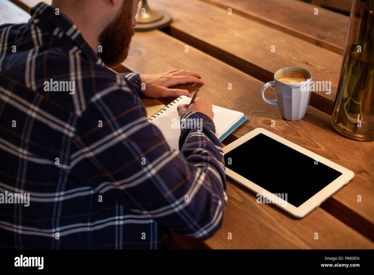 Young bearded businessman sits in cafe, home at table and writes in notebook, near lies tablet computer with black screen. Man is working, studying. - Stock Image