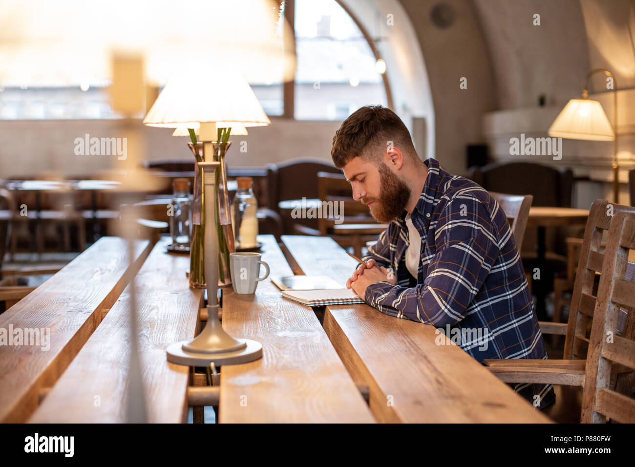 Young bearded businessman sits in cafe, home at table and writes in notebook, near lies tablet computer. Man is working, studying. - Stock Image