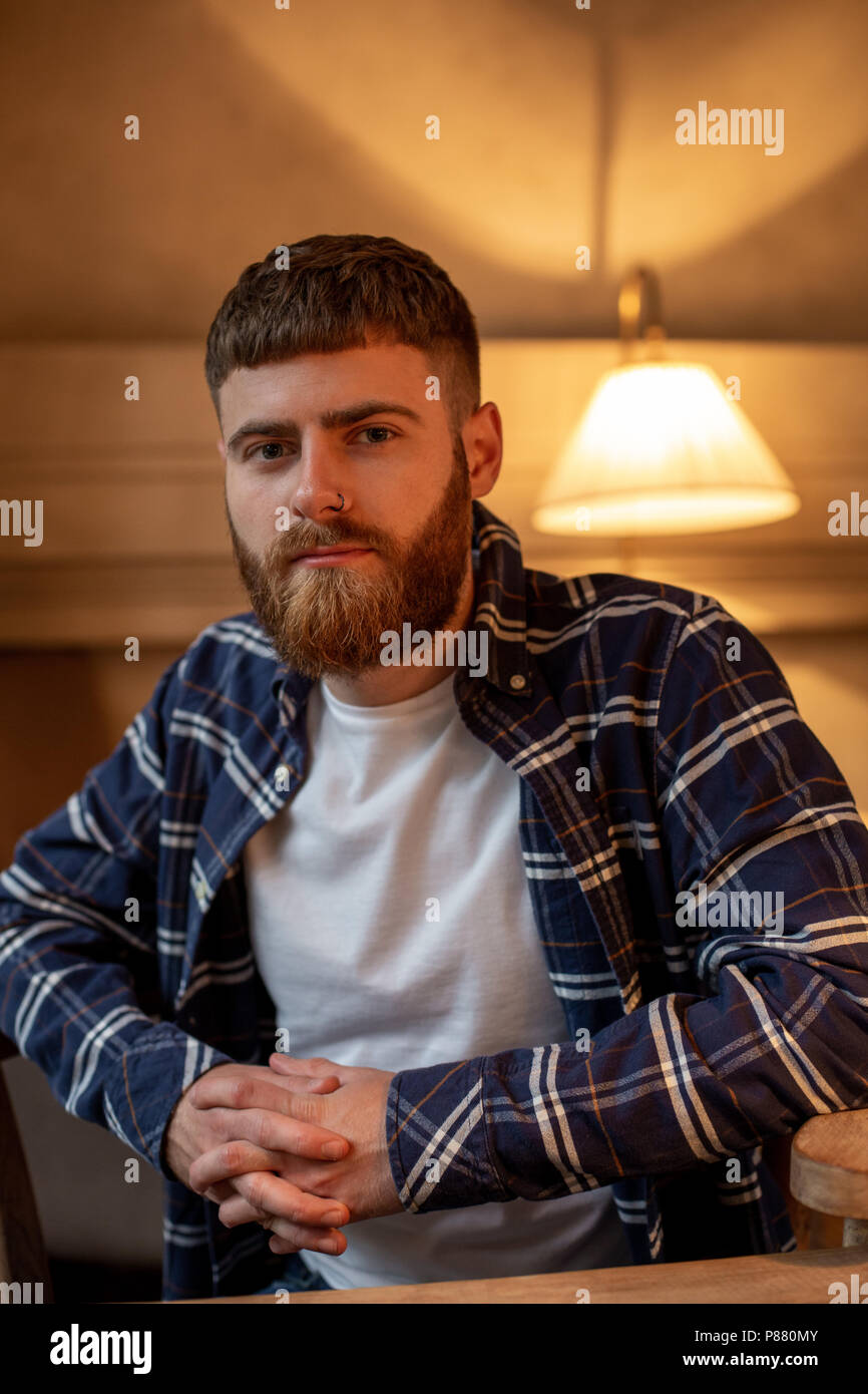 Portrait handsome bearded man wearing plaid shirt at modern cafe. - Stock Image