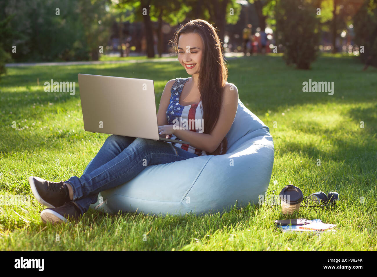 Young cute girl with laptop, sit on bean bag in garden or park, on green grass. Online shopping concept - Stock Image