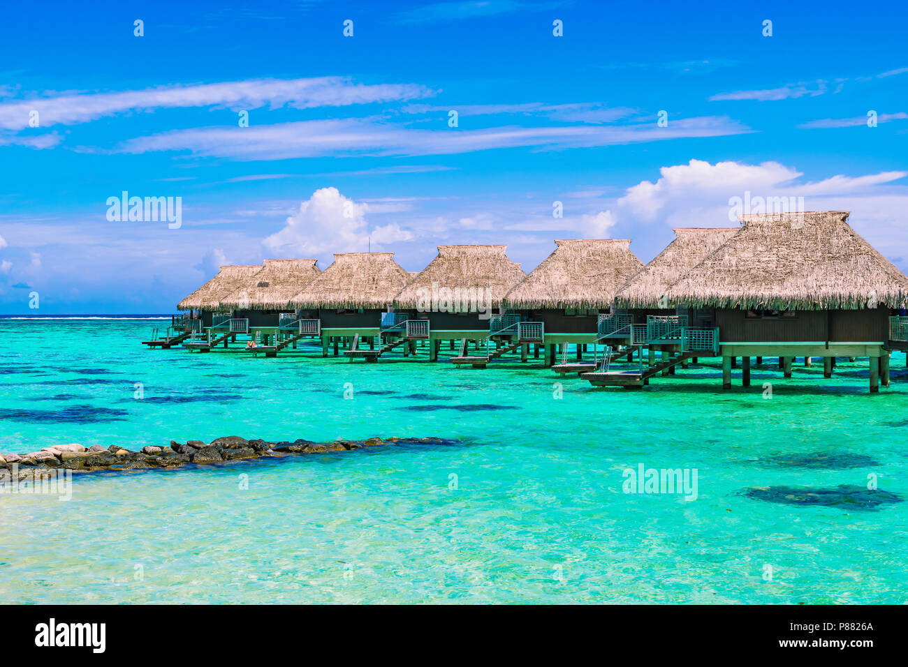 Luxury beach travel vacation concept: Overwater bungalows on turquoise coral reef lagoon ocean close to the beach. - Stock Image
