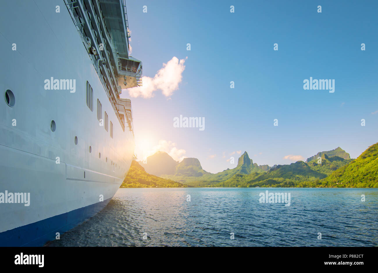 Side view of anchored cruise ship at sunset. Mountain background. Stock Photo