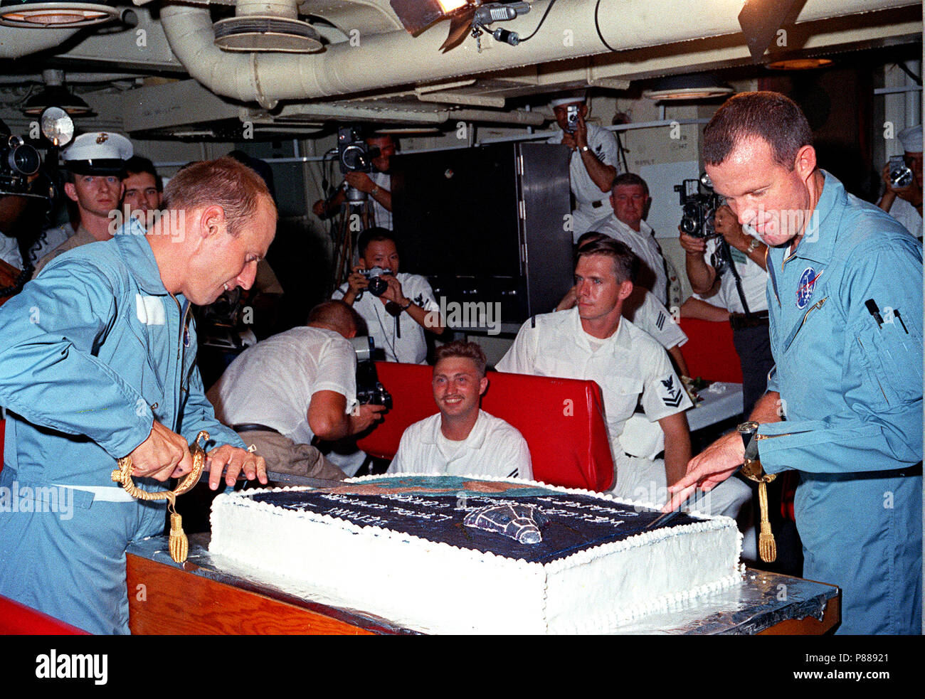 Astronauts Charles Conrad Jr. (left) and L. Gordon Cooper Jr. prepare to slice into the huge cake prepared for them by the cooks onboard the aircraft carrier USS Lake Champlain. Stock Photo