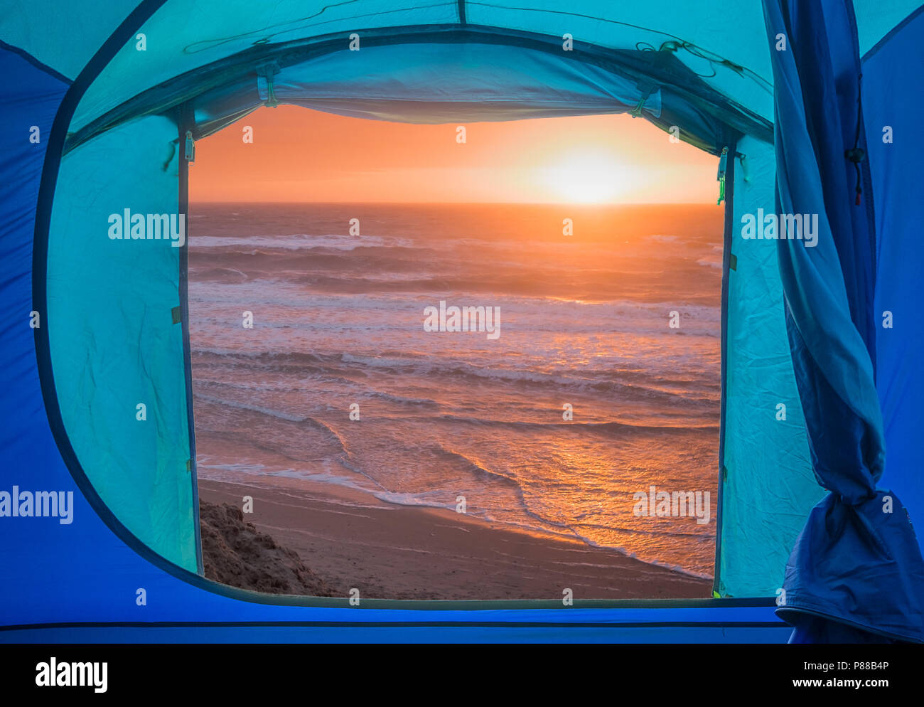 View from inside a tent onto a sunset over a beach and sea, Isle of Mull, Scotland. Stock Photo