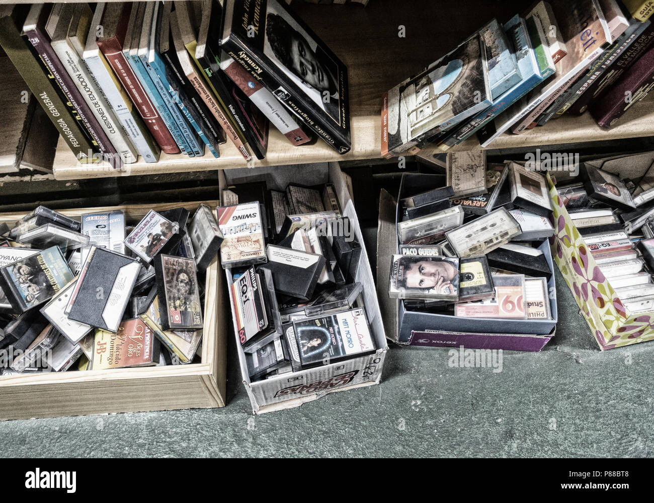 Boxes of cassette tapes and books in charity shop in Spain - Stock Image