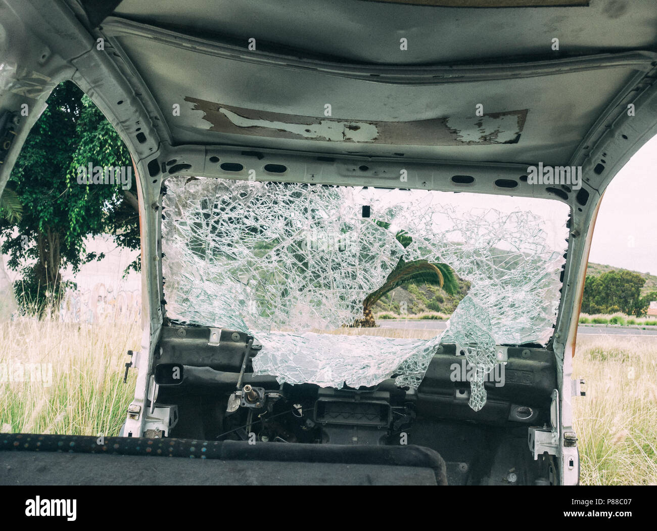 Broken windscreen on abandoned car in countryside - Stock Image