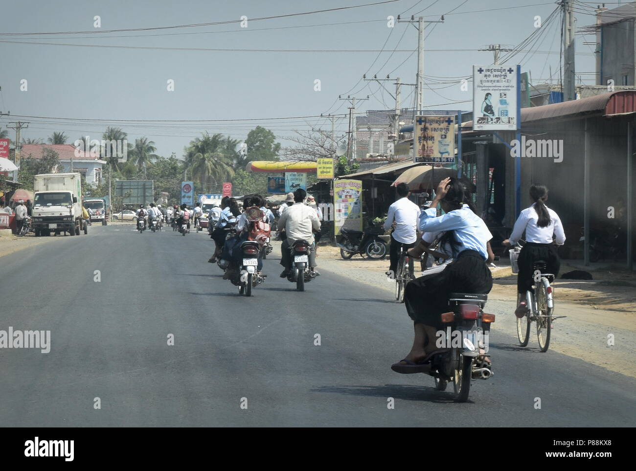 Rural Cambodia school students commute back home using bicycles and motorcycles on a public road - Stock Image