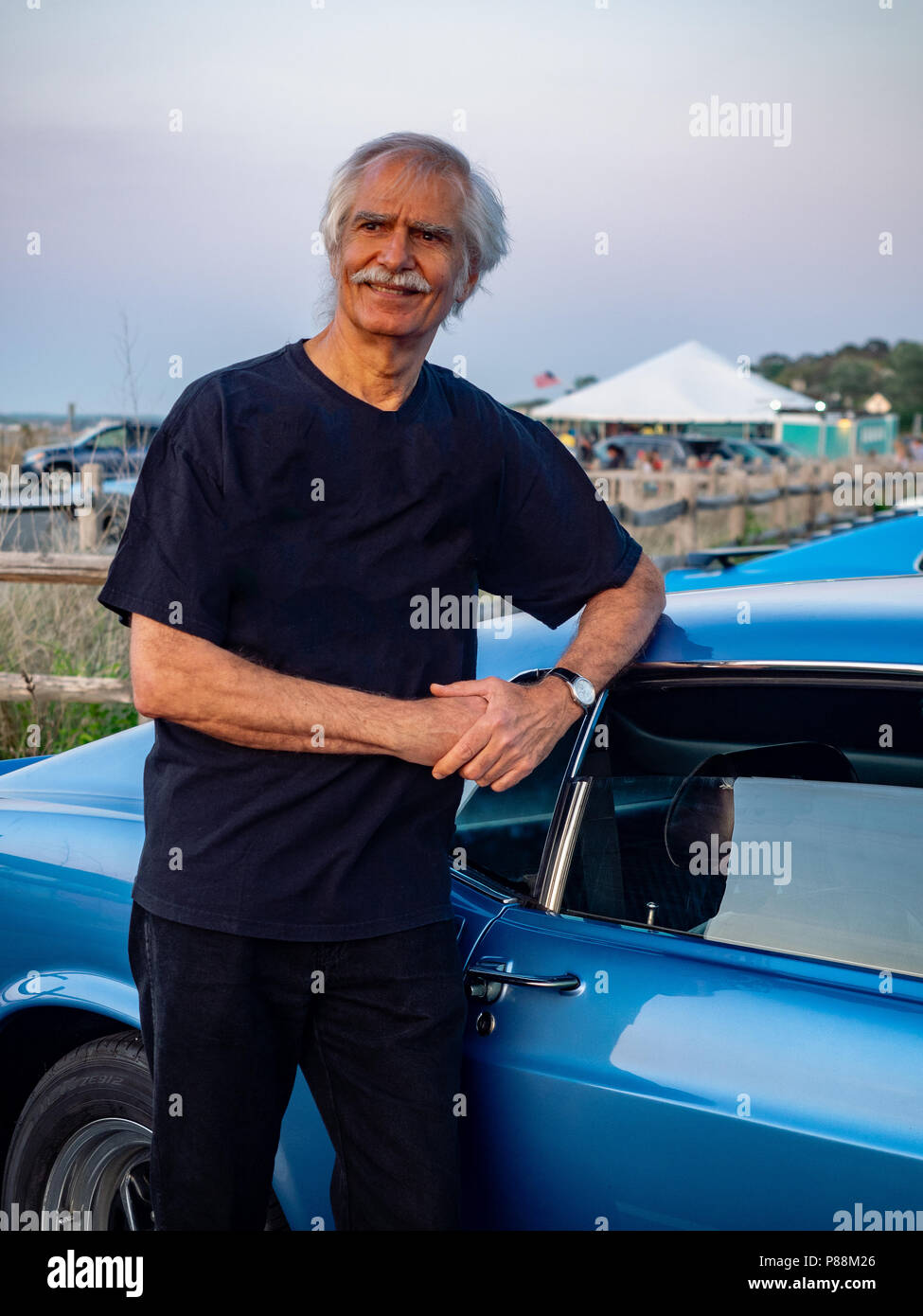 Man leaning against his 1969 blue classic Mustang at car show, The Hamptons, New York, USA. - Stock Image