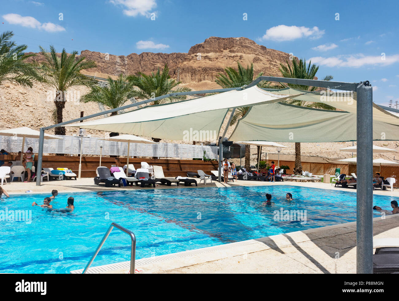 outdoor, partially shaded swimming pool at a hotel in Ein Bokek on the Dead Sea with desert mountain in the background - Stock Image