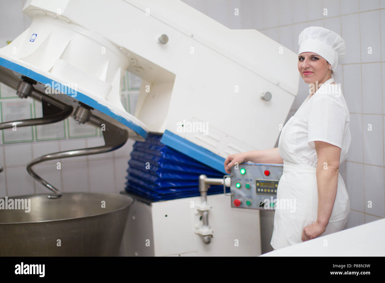 Belarus, the city of Gomel, on April 26, 2018. Gomel plant for the production of bread.Woman cook with industrial mixer.The worker of a bakery - Stock Image