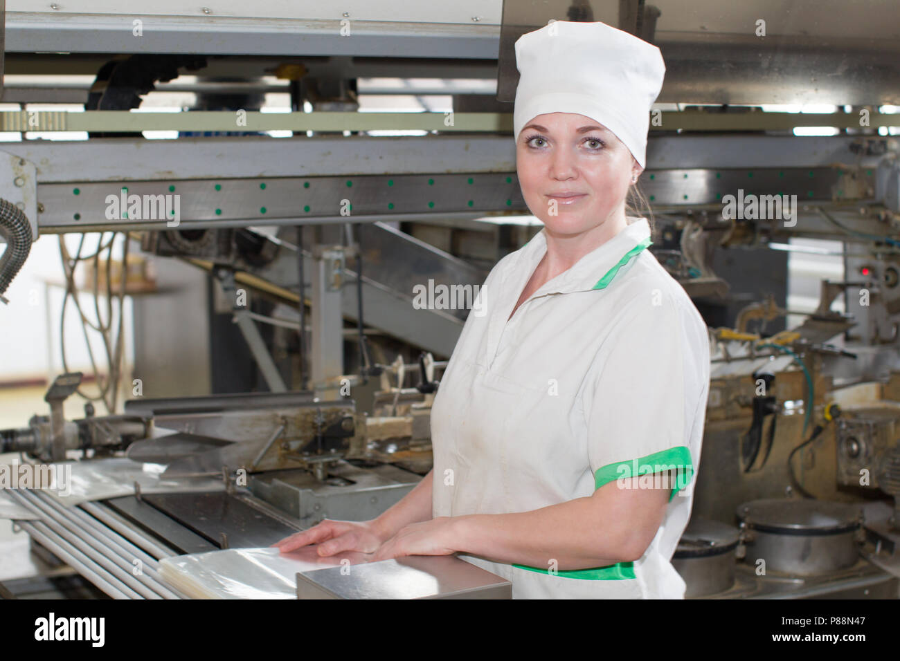 Belarus, the city of Gomel, on April 26, 2018. Gomel plant for the production of bread.Line for packing bread with a worker - Stock Image