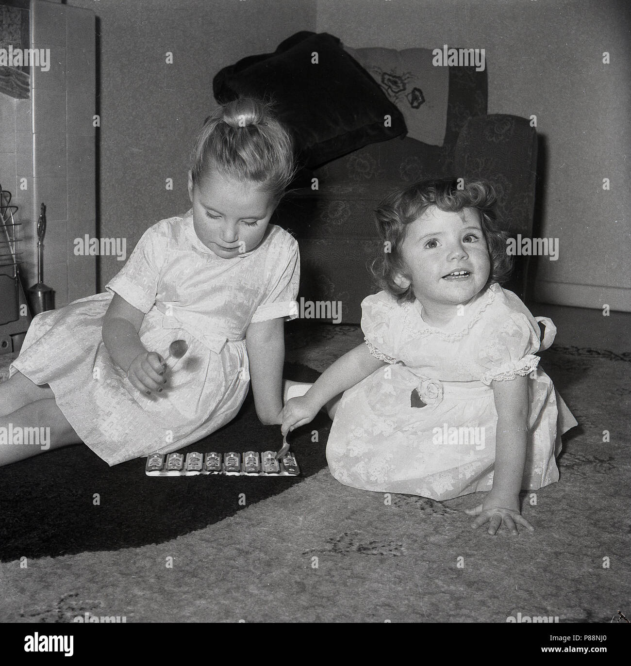 1950s, historical, two young girls sitting together on the floor of a living room playing with a small musical toy, a metal xylophone, - Stock Image