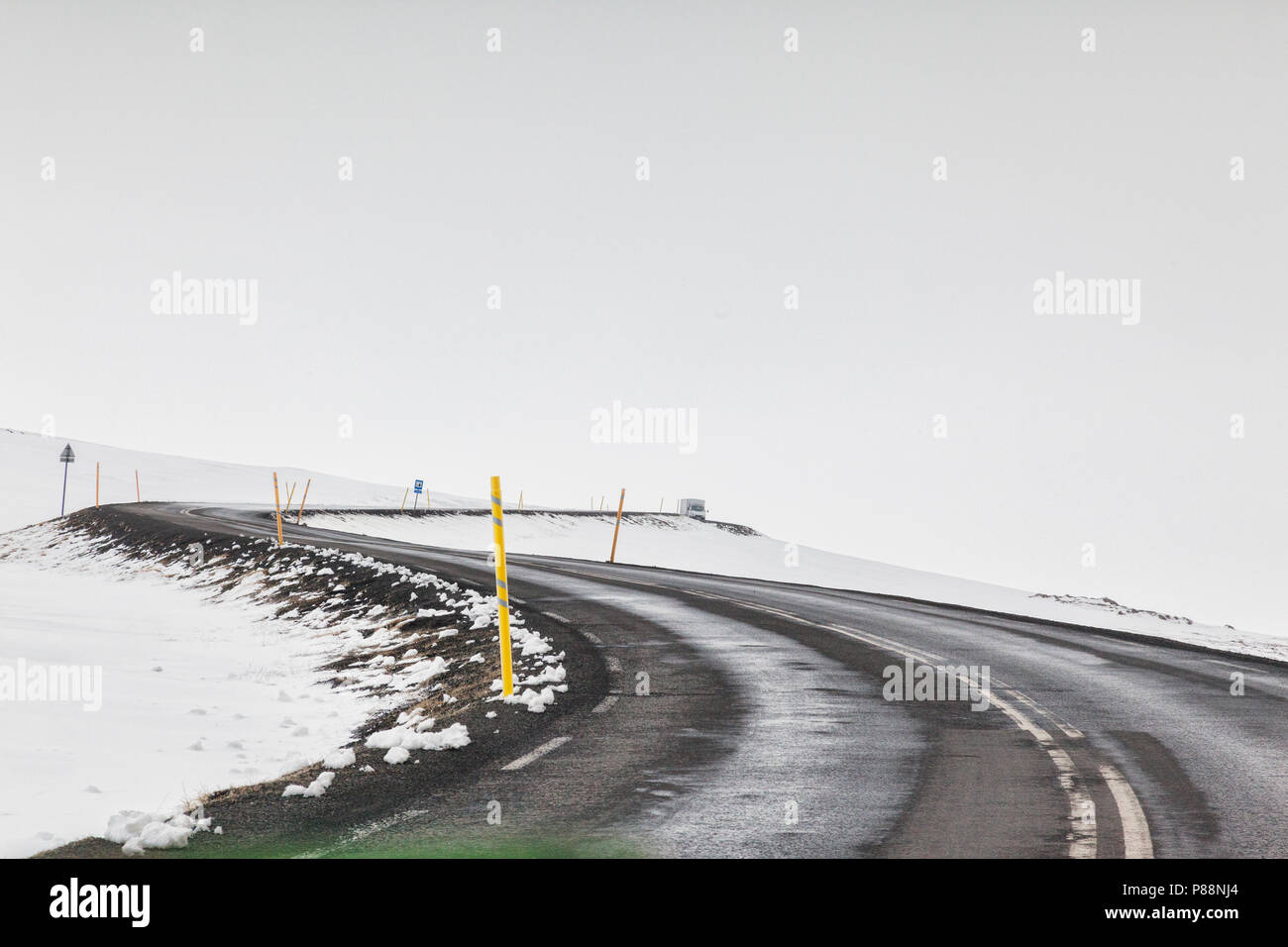 Through the windscreen shot of a tarmac road in East Iceland in foggy weather conditions, with a double bend and a distant truck or lorry. - Stock Image