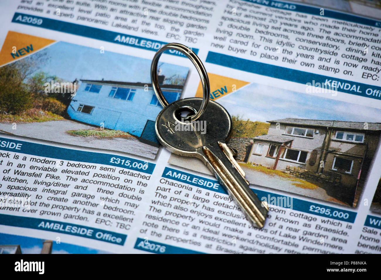 single key on top of adverts for property in the lake district cumbria england uk - Stock Image