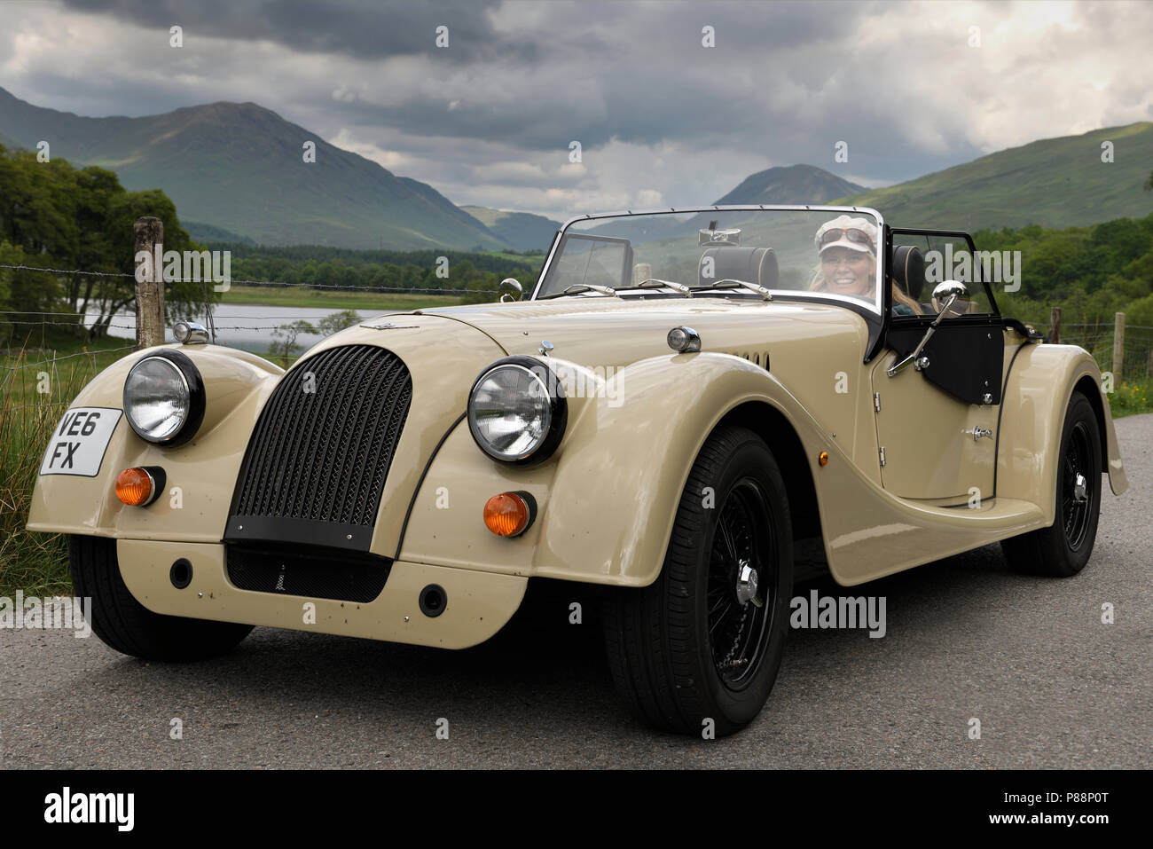 Woman in a hand made wood shell Morgan roadster car in the Scottish Highlands near Kilchurn Castel at Loch Awe Scotland UK - Stock Image