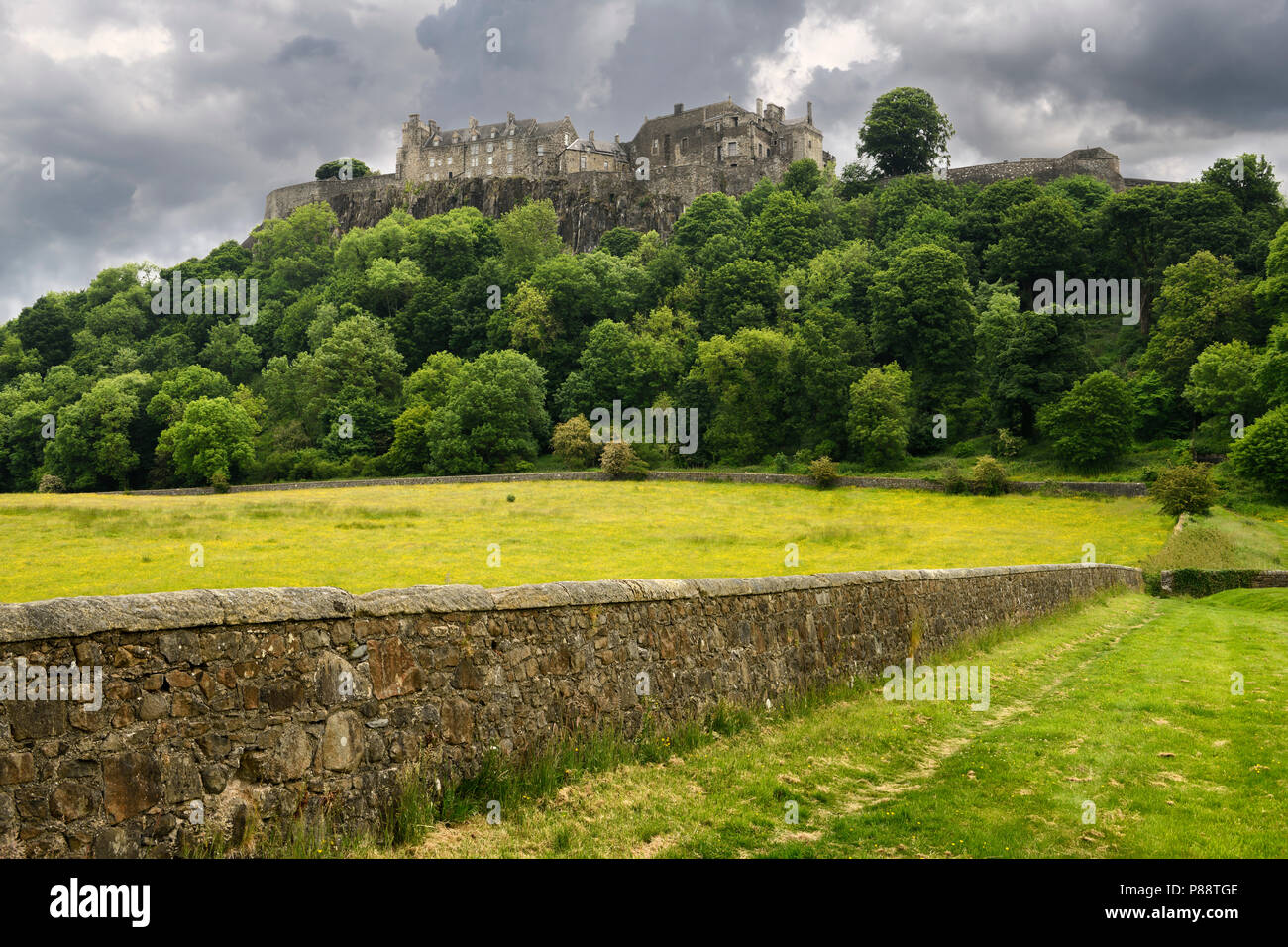 Stirling Castle on the cliff at Castle Hill in Stirling Scotland with stone wall of sheep pasture with dark clouds - Stock Image