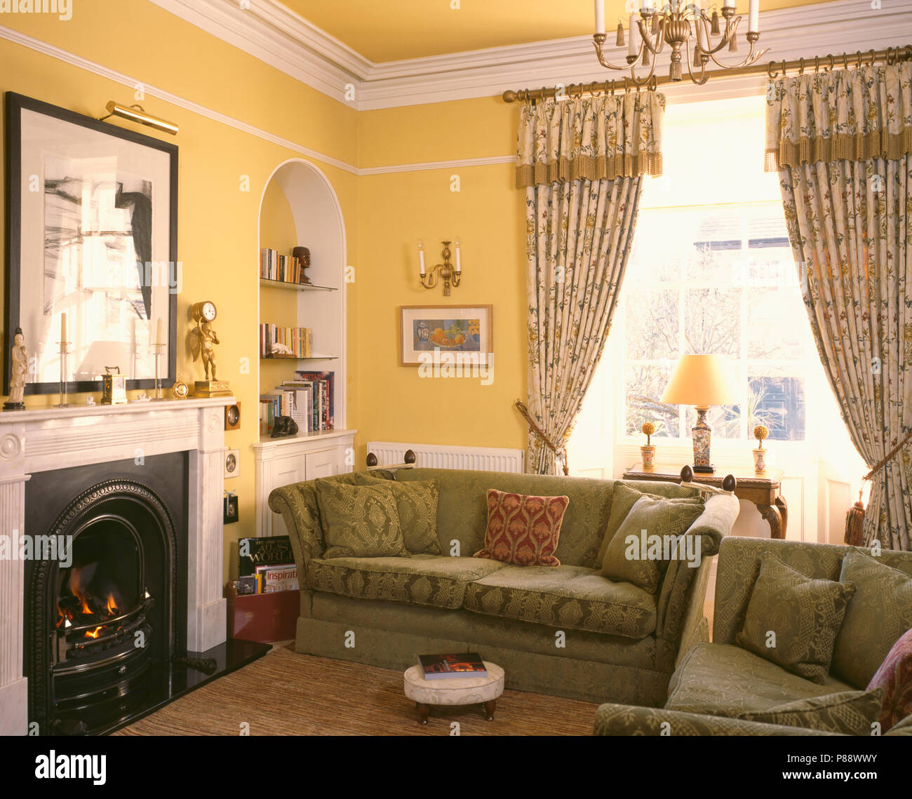 Patterned Curtains And Green Sofas Beside Fireplace In Yellow Livingroom