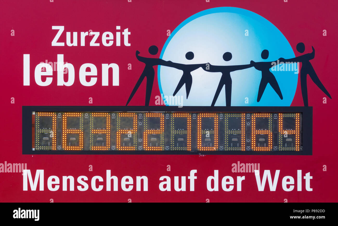 Hannover, Germany, July 7., 2018: Digital display with the number of people on earth (Translation: At the moment there are..... people in the world),  - Stock Image