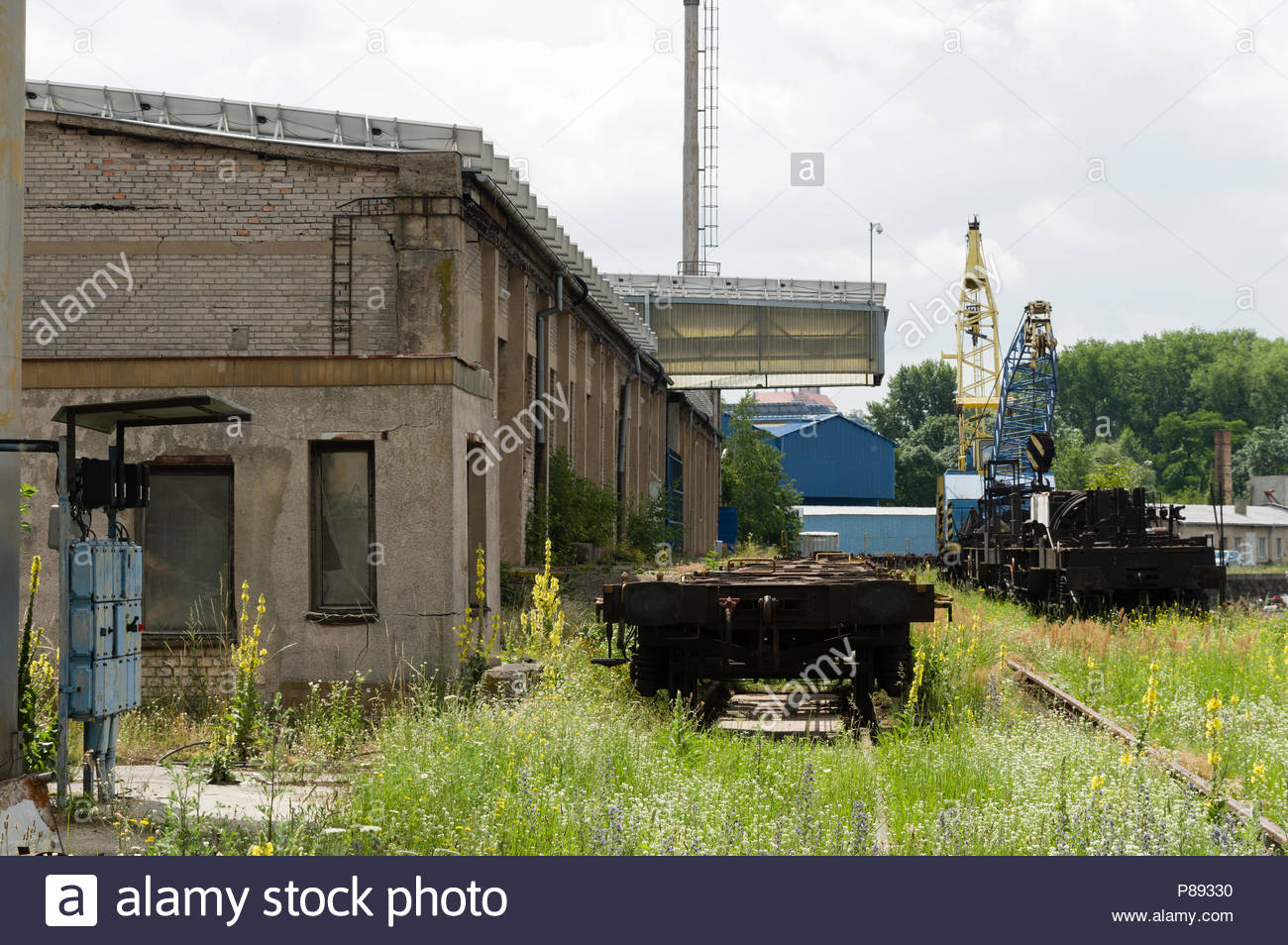 Abandoned looking industrial shipyard with large crane and railtracks - Stock Image