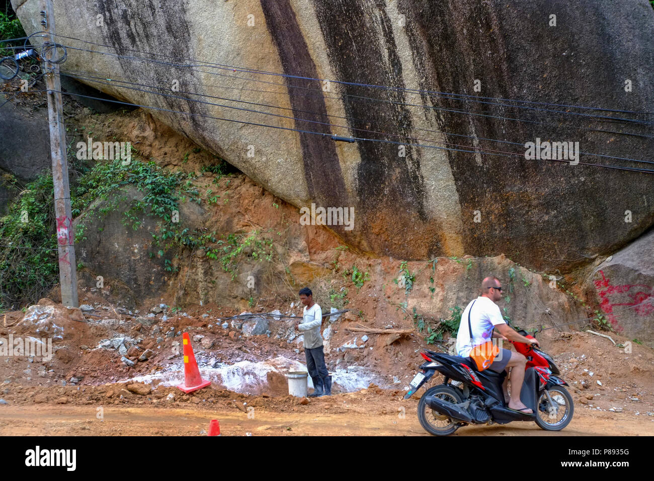 Construction Workers from Myanmar are building new roads through the jungles covering the mountains of the Thai island Koh Phangan, Thailand Stock Photo