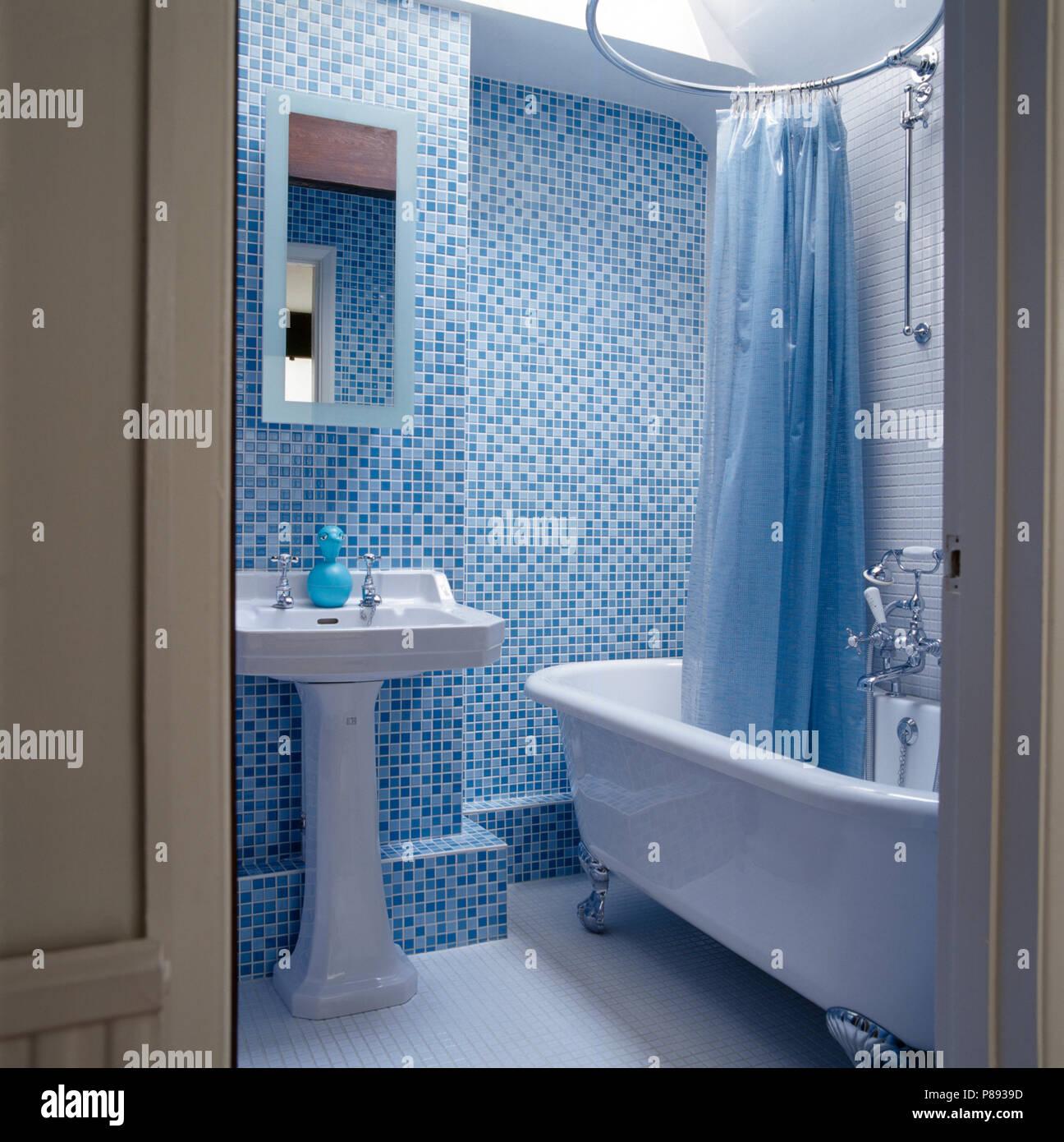 Blue plastic shower curtain above roll top bath in a blue mosaic ...