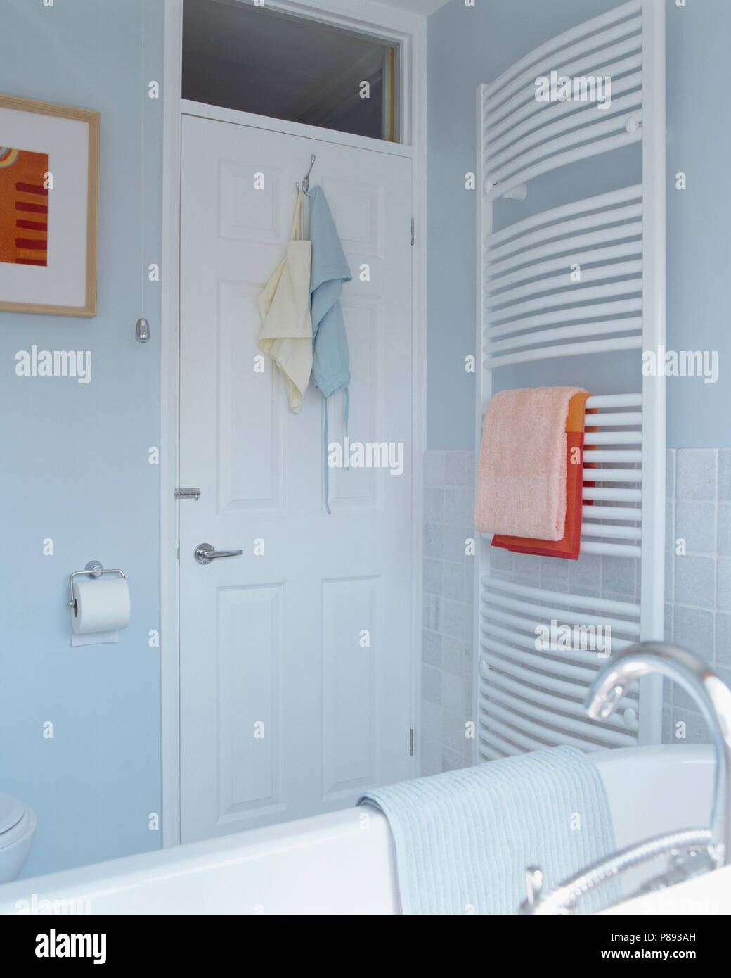 White Towel Rail On Wall Beside Door In Corner Of Modern Pastel Blue Bathroom