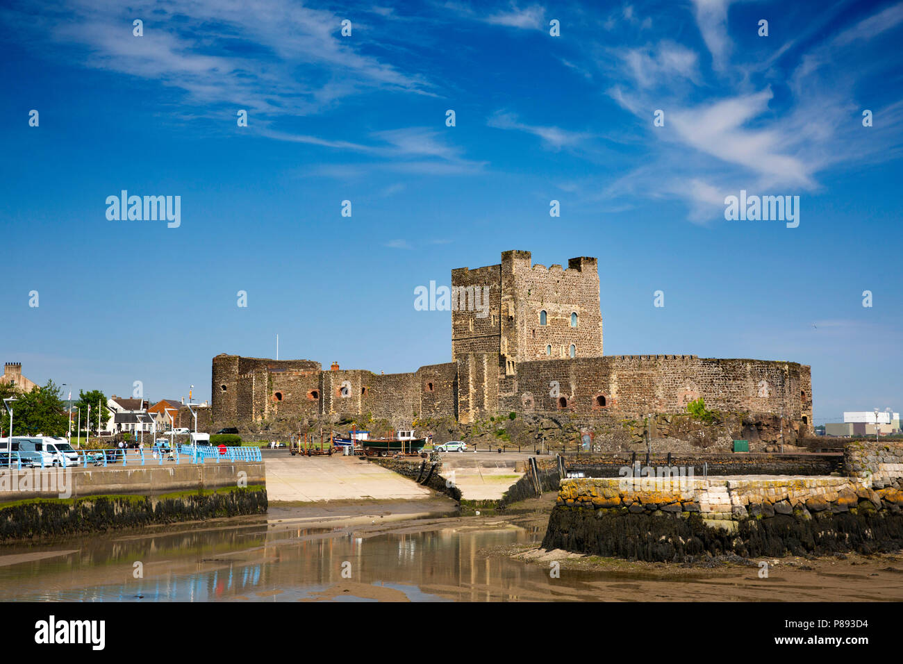 UK, Northern Ireland, Co Antrim, Carrickfergus, Norman Castle from across the harbour at low tide - Stock Image