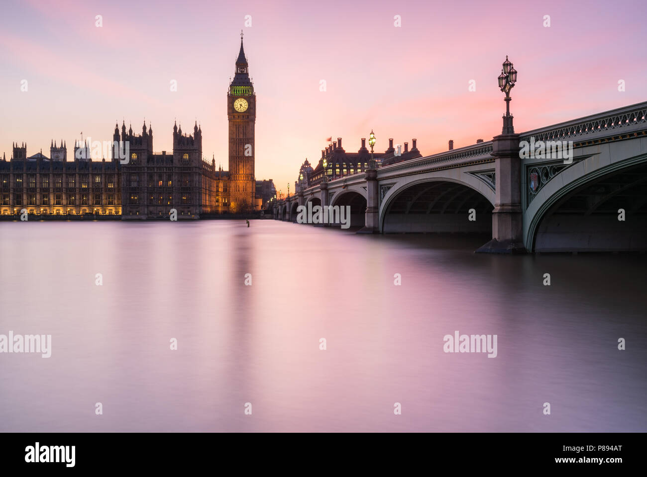 Magenta sunset over Big Ben and the Houses of Parliament in London including Westminster Bridge reflected in the smooth water of the River Thames - Stock Image