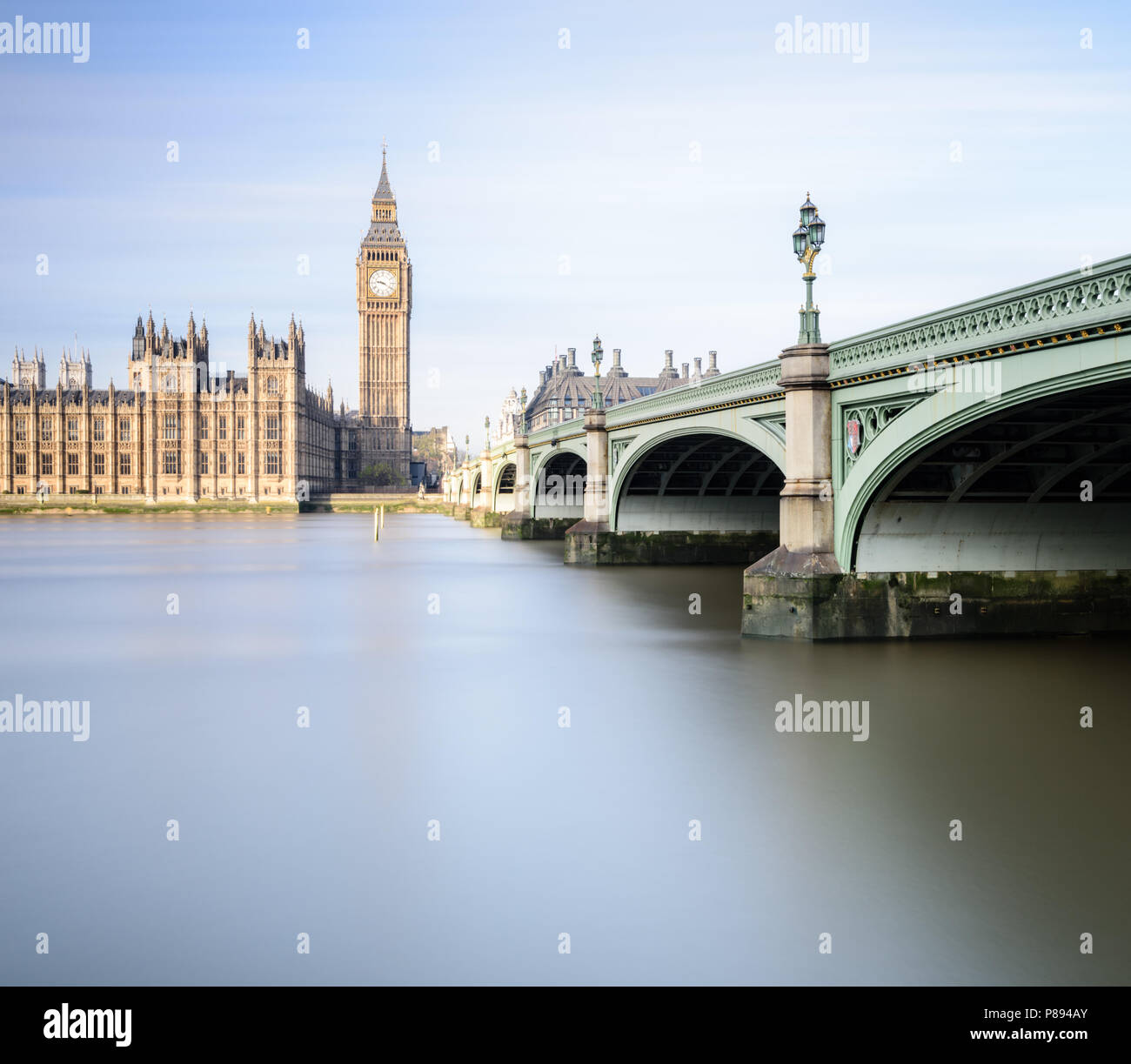 Big Ben and the Houses of Parliament in London including Westminster Bridge reflected in the smooth water of the River Thames on a bright sunny day Stock Photo