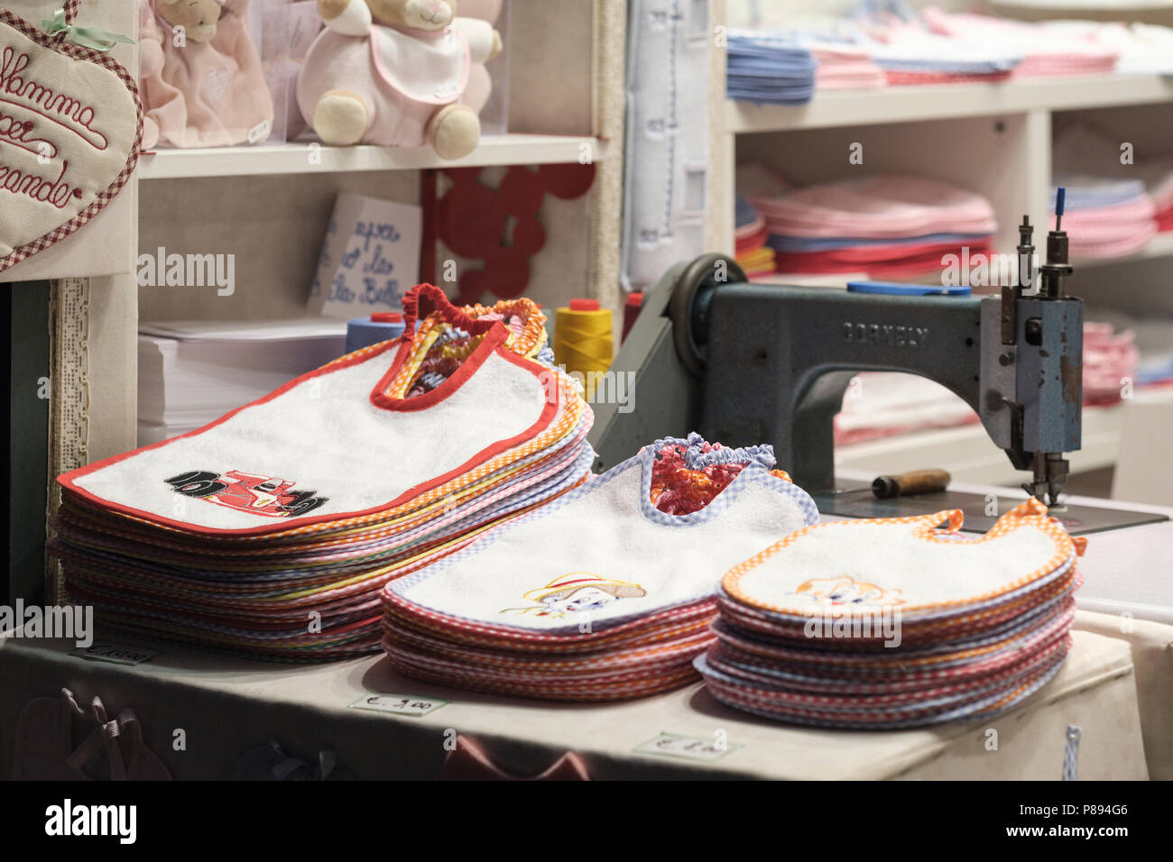 Babies bibs personally inscribed while you wait, old city shop in Lucca; Tuscany; Italy; Europe - Stock Image