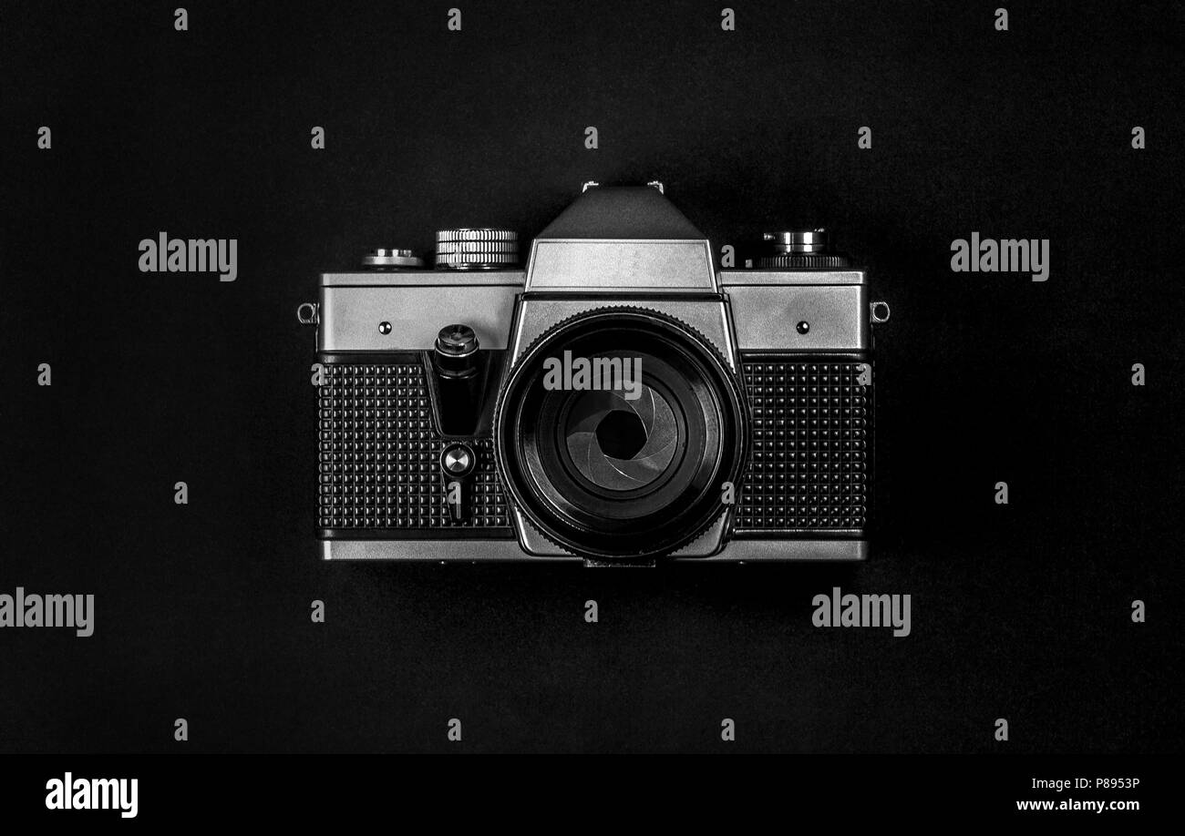 Old silver SLR film analog camera with lens and aperture - Stock Image